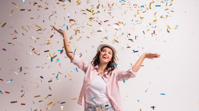 Cheerful young woman is stretching out her hands while confetti falling on her.